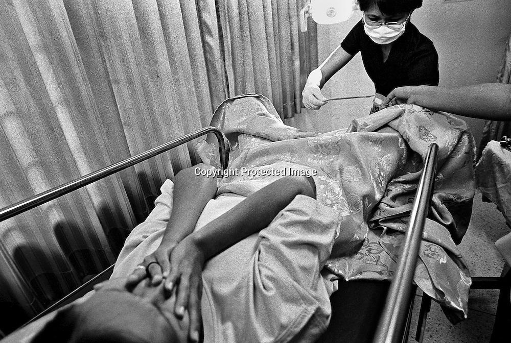 Die ausgebildete und erfahrene Krankenschwester 0Y aus BANGKOK unterstuetzt die Dorfbewohner aus BAAN GERDA und bildet die Krankenschwestern aus.  Seit Jahren arbeitet sie mit HIV-positiven Menschen..Hier untersucht sie PAI, 37 Jahre alt, auf Gebaermutterkrebs und entnimmt einen Abstrich. HIV-positive Frauen sind 10mal mehr gefaehrdet an Gebaehrmutterkrebs zu erkranken  als gesunde Frauen..Die Untersuchungen wurden in einem staatlichen Landhospital in der Naehe von BAAN GERDA unternommen. .Provinz Lop Buri, Thailand..OY, age 32, professional nurse works for many years with HIV patients. Her longtime experiences is helpful for the nurses and people in BAAN GERDA..OY is taking a swab from PAI, age 37, to check the womb. Women who are infected by HIV are tentimes more at risk to get womb-cancer. At a small statehospital  near by the village BAAN GERDA.Province Lop Buri, Thailand
