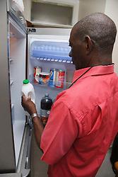 Elderly black man at home in kitchen getting milk out of fridge