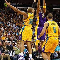 February 5, 2011; New Orleans, LA, USA; Los Angeles Lakers shooting guard Kobe Bryant (24) shoots over New Orleans Hornets power forward David West (30) and forward Sasha Pavlovic (6) during the second quarter at the New Orleans Arena.   Mandatory Credit: Derick E. Hingle
