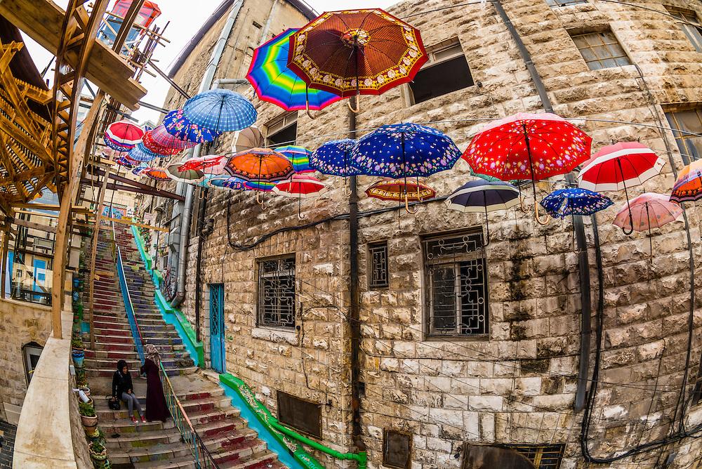 Umbrellas hanging above a narrow staircase in Amman, Jordan.