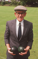 Elderly man standing on bowling green holding bowls,