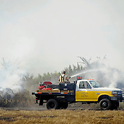 Firefighters work to contain in the Henderson community of Pike County, Ala., Thursday, Aug. 7, 2014. Firefighters from Henderson, Goshen and Springhill Volunteer Fire Departments responded to the scene. Approximately 25 hay bales were burned in the blaze that started from a machine malfunction. (Photo/Thomas Graning)