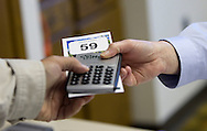 Hertz Real Estate Services executive assistant Denise Vallandingham (right) hands a bidder number and calculator to an attendee before the start of a farm auction at the Eagle Grove Masonic Lodge in Eagle Grove, Iowa on Thursday, October 18, 2012.