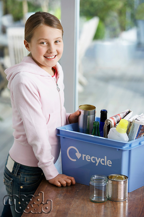 Girl (10-12) putting empty vessels into recycling container smiling side view