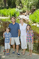 Full length portrait of couple with children standing against lake
