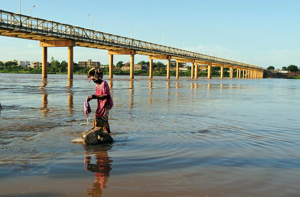 Une femme lave des vêtements dans le Fleuve Sénégal sous le pont qui traverse le fleuve en centre ville..Kayes, Mali. 10/09/2010..Photo © J.B. Russell