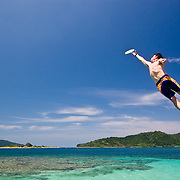 Mac Stone jumps off a dock in Cayos cochinos, Honduras.