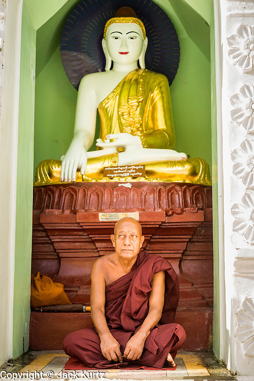 15 JUNE 2013 - YANGON, MYANMAR: A Buddhist monk prays at Shwedagon Pagoda. The Shwedagon Pagoda is officially known as Shwedagon Zedi Daw and is also called the Great Dagon Pagoda or the Golden Pagoda. It is a 99 metres (325 ft) tall pagoda and stupa located in Yangon, Burma. The pagoda lies to the west of on Singuttara Hill, and dominates the skyline of the city. It is the most sacred Buddhist pagoda in Myanmar and contains relics of the past four Buddhas enshrined: the staff of Kakusandha, the water filter of Koṇāgamana, a piece of the robe of Kassapa and eight strands of hair fromGautama, the historical Buddha. The pagoda was built between the 6th and 10th centuries by the Mon people, who used to dominate the area around what is now Yangon (Rangoon). The pagoda has been renovated numerous times through the centuries. Millions of Burmese and tens of thousands of tourists visit the pagoda every year, which is the most visited site in Yangon.   PHOTO BY JACK KURTZ