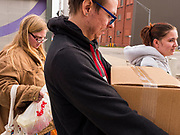 """26 MARCH 2020 - DES MOINES, IOWA: People walk away with food packages at a Des Moines Area Religious Council (DMARC) mobile pantry food distribution in the DART Central Station in Des Moines. DMARC is doing weekly food distribution at the transit station. They are using """"social distancing"""" guidelines by asking clients to not get too close to their workers. DMARC used to let clients walk through mobile pantry to select groceries, but now clients wait while workers bags of foodstuffs. On Thursday morning, 24 March, Iowa reported 175 confirmed cases of the Coronavirus (SARS-CoV-2) and COVID-19. Restaurants, bars, movie theaters, places that draw crowds are closed until 07 April. The Governor has not ordered """"shelter in place""""  but several Mayors, including the Mayor of Des Moines, have asked residents to stay in their homes for all but the essential needs. People are being encouraged to practice """"social distancing"""" and many businesses are requiring or encouraging employees to telecommute.        PHOTO BY JACK KURTZ"""
