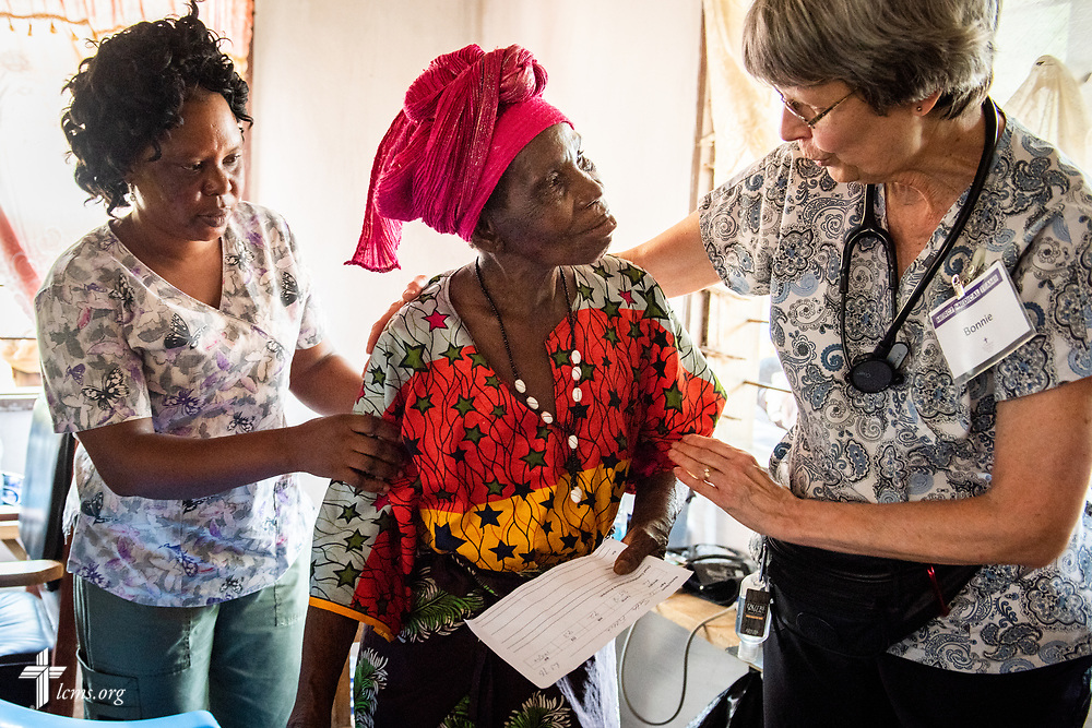 A patient smiles back at Bonnie Hartman, a member of Faith Lutheran Church, Godfrey, Ill., as she's helped from vitals toward the triage waiting area on the third day of the LCMS Mercy Medical Team on Wednesday, May 9, 2018, in the Yardu village outside Koidu, Sierra Leone, West Africa. LCMS Communications/Erik M. Lunsford