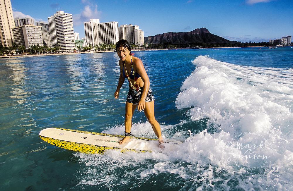Woman surfing at Waikiki Beach, Honolulu, Oahu, Hawaii. Diamond Head in background.