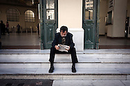 Greece, April 2013 - A man is reading his newspaper just outside the Monastiraki train station in Athens.