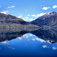 Lake Moeraki Reflection in Haast, New Zealand <br /> There are almost 4,000 lakes in New Zealand. Those near the Southern Alps seem as uninhabited and unspoiled as they were when first cut by glaciers. This gorgeous example is Lake Moeraki near Haast on the west coast of the South Island. Nearby is a rare Kiwi colony (think small bird with a long beak and not the fruit).