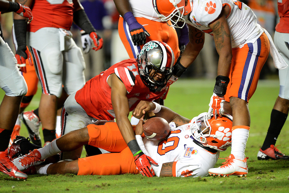 January 3, 2014: Tajh Boyd #10 of Clemson is tackled by Vonn Bell #11 of Ohio State during the NCAA football game between the Clemson Tigers and the Ohio State Buckeyes at the 2014 Orange Bowl in Miami Gardens, Florida. The Tigers defeated the Buckeyes 40-35.