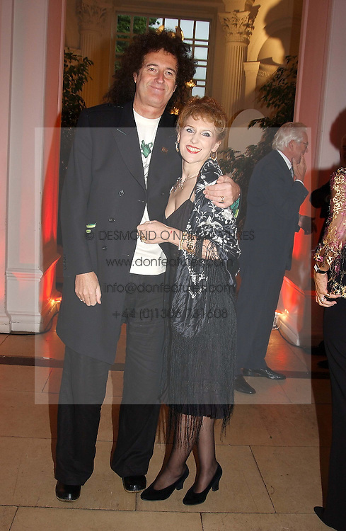 Musician BRIAN MAY and actress ANITA DOBSON at a party to celebrattte the 150th anniversary of Kensington Palace Gardens in aid of the British Red Cross held at The Orangery, Kensington Palace, London on 7th July 2004.