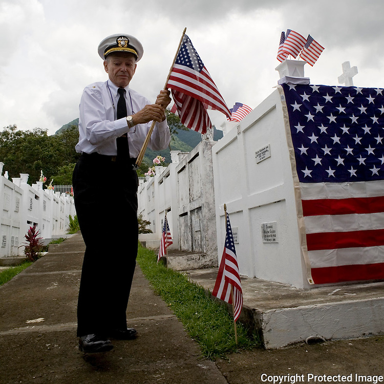 Mel Goldberg of the American Legion laying flags for each American Legion Vet who has died this past year at the cememtary in Escazu for a Memeorial Day Service honoring Veterans.
