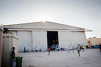 "HAL FAR, MALTA - JUNE 21: Immigrants play soccer at the Hangar Open Center in Hal Far (which translates as ""Rat's Town"") on June 21, 2011. The Hangar Open Center is a field with an ex-aircraft hangar which includes Swiss Red Cross tents in a dark, non lit space, and external containers. The conditions are very poor and the has inflamable oil on the floor.<br /> <br /> The Open Centres in Malta serve as a temporary accomodation facility, but they ended becoming permanent accomodation centres, except for those immigrants who receive subsidiary protection or refugee status and that are sent to countries such as the United States, Germany, Poland, and others. All immigrants who enter in Malta illegally are detained. Upon arrival to Malta, irregular migrants and asylum seekers are sent to one of three dedicated immigration detention facilities. Once apprehended by the authorities, immigrants remain in detention even after they apply for refugee status. detention lasts as long as it takes for asylum claims to be determined. This usually takes months; asylum seekers often wait five to 10 months for their first interview with the Refugee Commissioner. Asylum seekers may be detained for up to 12 months: at this point, if their claim is still pending, they are released and transferred to an Open Center.<br /> <br /> <br /> Gianni Cipriano for The New York Times"