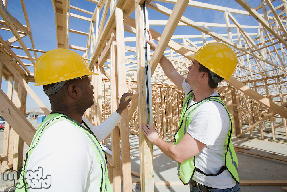 Two construction workers measuring building framework