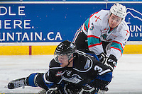 KELOWNA, CANADA - APRIL 12: Ryan Gagnon #3 of Victoria Royals falls to the ice while being checked by Riley Stadel #3 of Kelowna Rockets on April 12, 2016 at Prospera Place in Kelowna, British Columbia, Canada.  (Photo by Marissa Baecker/Shoot the Breeze)  *** Local Caption *** Ryan Gagnon; Riley Stadel;