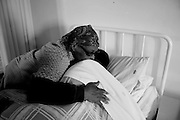 Maria is hugged by her mother after being admitted  at the Footprints Hospice , Orlando East, Soweto South Africa  17 August 2009. Footprints hospice was founded by  the Soweto Retired Professional Society (SRPS) in August 2004 by retired nurses from Chris Hani Baragwanath Hospital.  .