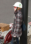 A mod girl with a white helmet on, standing next to a scooter, in profile, London, UK, 2008