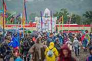 A polar bear wattches as crowds trudge through the rain. The 2016 Glastonbury Festival, Worthy Farm, Glastonbury.