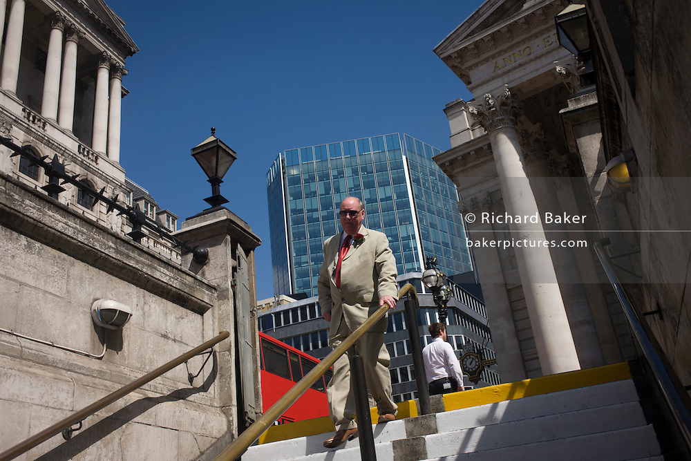 At Cornhill in the City of London, a businessman descends the steps into the London Underground, at Bank station, below the Bank of England.
