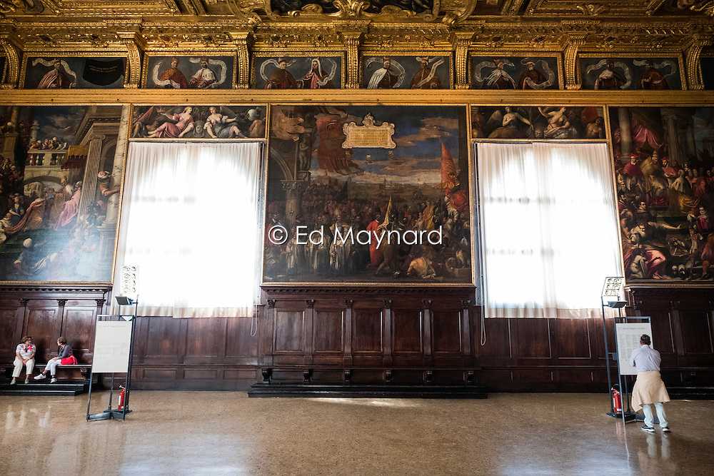 Tourists viewing the artwork and decoration inside the Doge's Palace, San Marco, Venice, Italy.<br />