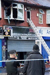 © Licensed to London News Pictures. Manchester, UK 16/05/2012: Police at the scene where twenty five firefighters tackle a blaze at a flat above H&A Tailors on the A34 Kingsway in Levenshulme. Two people were evacuated from the flat and taken to hospital. The main city-centre route was closed in both directions. Photo credit : Joel Goodman/LNP
