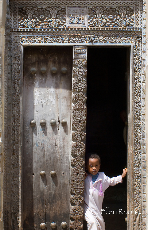 A young boy looking out from a traditional wood carved 'Arab' door. Stone Town,  Zanzibar, Tanzania