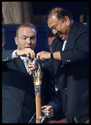 Image licensed to i-Images Picture Agency. 23/07/2014. Glasgow, United Kingdom. Commonwealth Games Federation President  Prince Imran struggles to take The Queen's message from the baton watched by Sir Chris Hoy   at the Commonwealth Games opening ceremony in  Glasgow. Picture by Stephen Lock / i-Images