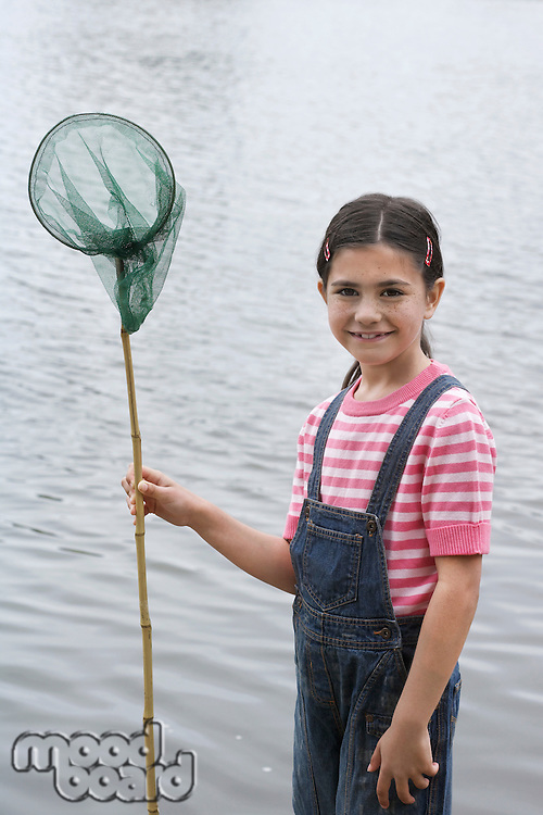 Girl (5-6) with fishing net by water portrait