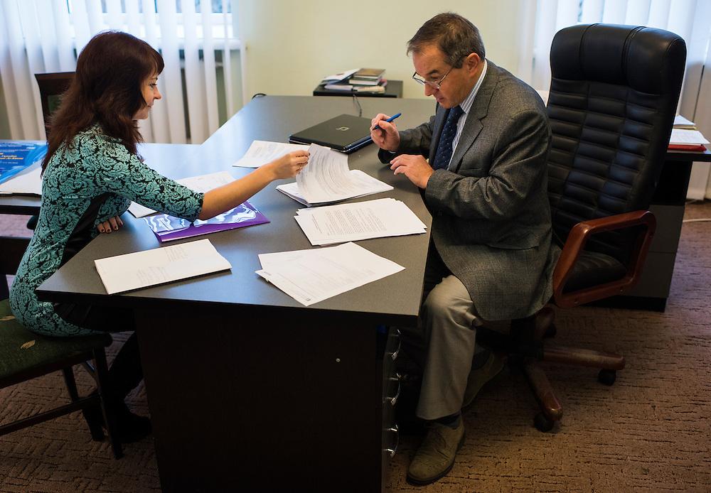 Michel Terestchenko signe des papiers pr&eacute;par&eacute;s par Alyona Demicheva, &agrave; gauche, son ancienne collaboratrice &agrave; Linen of Desna, d&eacute;sormais secr&eacute;taire de la mairie dans sa bureau le 7 d&eacute;cembre 2015 &agrave; Hlukhiv, Ukraine.<br /> <br /> Michel Terestchenko signs papers prepared by his assistant, Alyona, left, in his office on December 7, 2015 in Hlukhiv, Ukraine.