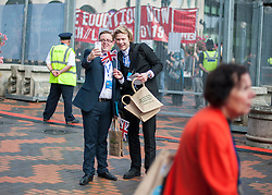 © Licensed to London News Pictures. 28/09/2014. Birmingham, UK. Two delegates take a selfie on their phones against a backdrop of a protest over education.  The Conservative Party Conference in Birmingham 28th September 2014. Photo credit : Stephen Simpson/LNP