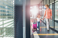 Portrait of mature woman walking with her daughter in arrival area at airport with lens flare