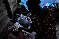 """Aliza Sikiliza (left) goes into labor in a dark room at Katsuva's farm. She was abducted by soldiers and held in captivity as a sex slave for five months before escaping. She is about to have the baby of one of her rapists. Katsuva listens with a stethoscope to the moaning woman's belly, and then leaves her alone. """"Mamma Masika,"""" as Katsuva is called, says the farm has helped nearly 6,000 women since it opened in 2000. More women turn up at the farm every week, and some go into labor on the rough journey to the farm. (photo by Mary Calvert)"""