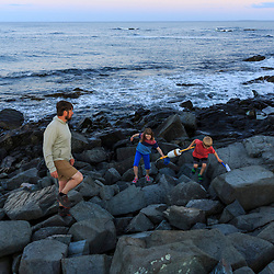 A man walks with his kids on the rocks at Seapoint Beach in Kittery, Maine.