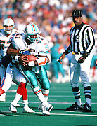 An NFL official looks on as Miami Dolphins fullback Keith Byars (41) tries to shake off a tackle attempt as he runs the ball during the 1994 NFL regular season football game against the Buffalo Bills on Oct. 9, 1994 in Orchard Park, N.Y. The Bills won the game 21-11. (©Paul Anthony Spinelli)
