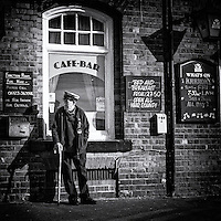 Elderley male pensioner standing with a walking stick outside a cafe-bar in England