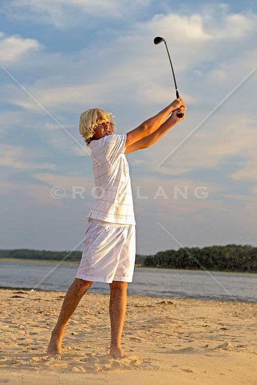 blond boy swinging a golf club on the beach in East Hampton, NY
