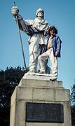 Mountaineer Reinhold Messner climbs on Scott's statue in Christchurch, New Zealand after skiing across Antarctica.