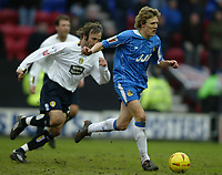 Photo: Chris Brunskill. Wigan Athletic v Leeds United.. Coca-Cola Championship. 19/02/2005. Jimmy Bullard of Wigan is chased by Sean Derry of Leeds.