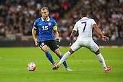 Estonia captain Ragnar Klavan goes pastt England's Theo Walcott during the UEFA European 2016 Qualifier match between England and Estonia at Wembley Stadium, London, England on 9 October 2015. Photo by Shane Healey.