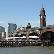 The Erie-Lackawanna Railroad and Ferry Terminal. Originally built in 1907 by the Delaware, Lackawanna and Western Railroad the building on the Hoboken waterfront allowed rail commuters to transfer to ferries to access New York City on the other side of the Hudson River. Part of the Jersey City, NJ skyline is visible in the rear. Hoboken, New Jersey, USA