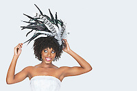 Beautiful African American bride wearing feather fascinator over gray background