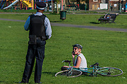 A Police PCSO patrols the common giving out low key advice on the Stay at Home guidance to the few people who are sitting and not exercising (albeit some only appear to start exercising on his approach) - Clapham Common is pretty quiet now Lambeth Council has taped up all the benches, put up signs and organised patrols by wardens. The 'lockdown' continues for the Coronavirus (Covid 19) outbreak in London.