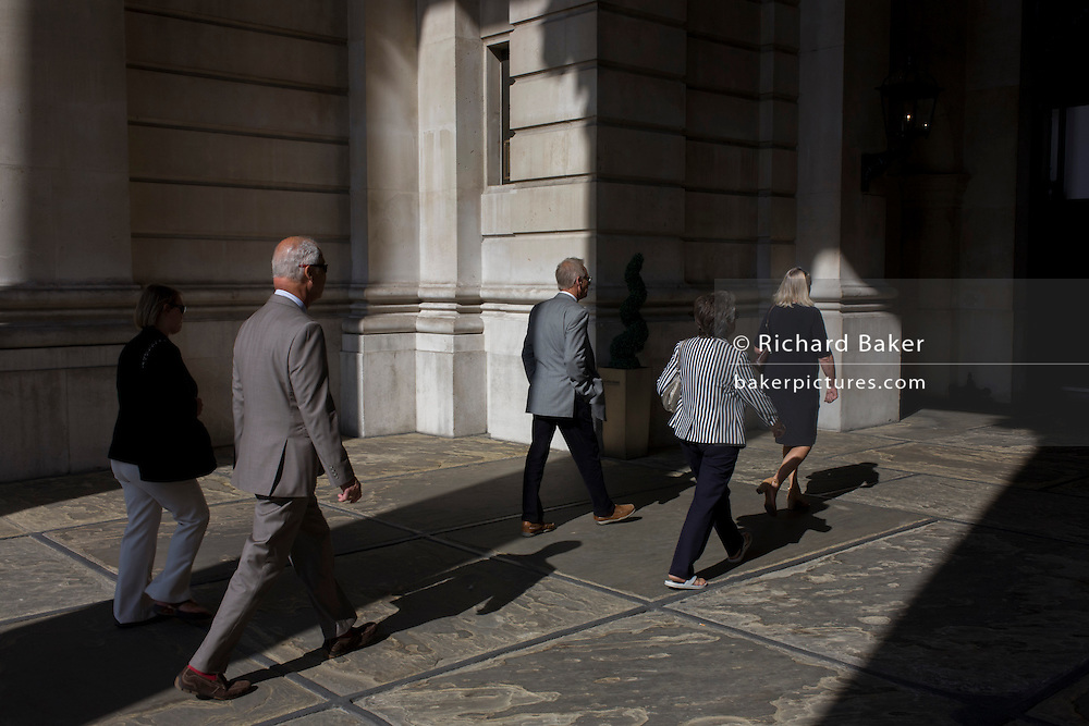People walk through sunlight at Cornhill in the City of London.