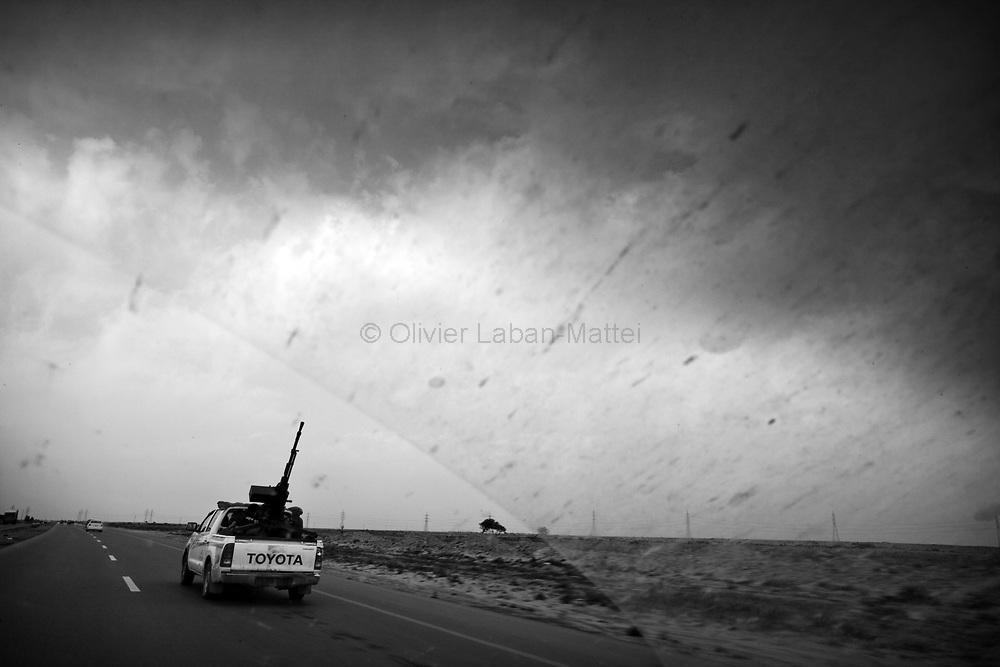 Des rebelles fuient en pick-up les tirs d'obus de l'armée kadhafiste, sur la route entre Brega et Aj Dabiya, le 30 mars 2011.
