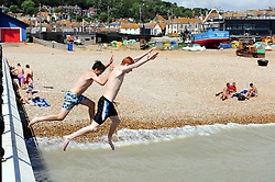 &copy; Licensed to London News Pictures. 17/07/2018<br /> Hastings, UK.<br /> Teenagers jumping off a small pier near the fishing boats.<br /> Hot heatwave weather in Hastings on the seafront as people enjoy their day.<br /> Photo credit: Grant Falvey/LNP