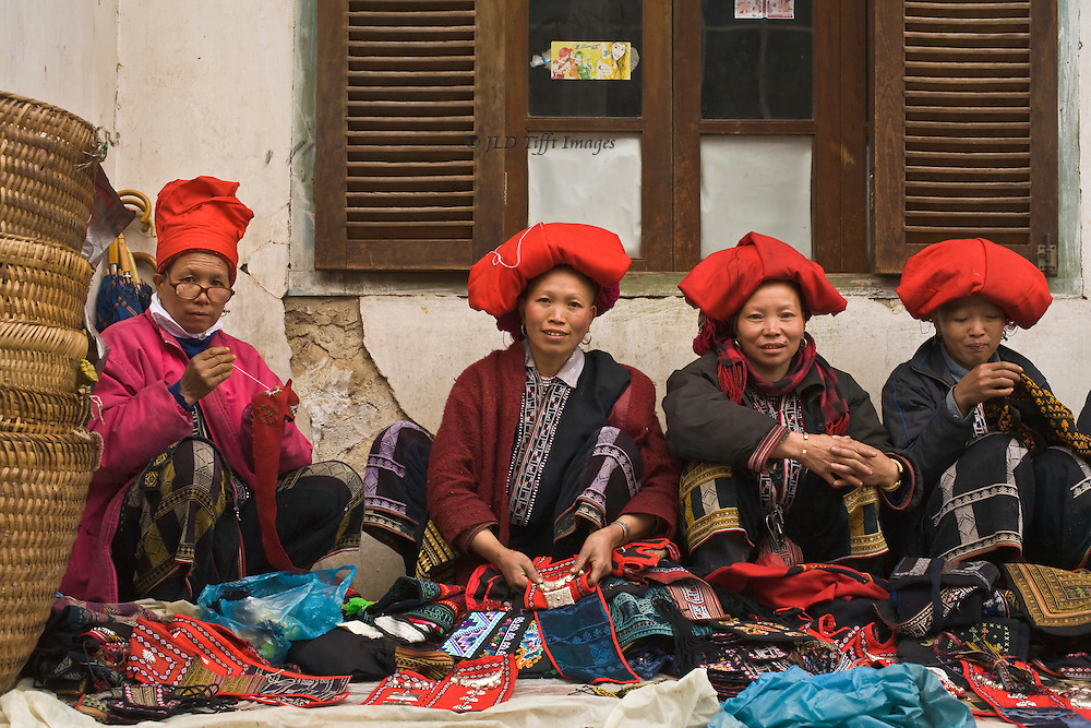 "Four ""Red Hmong"" women seated in a row on the sidewalk outside a building in Sa Pa, their needlework laid out in front of them.  They wear traditional clothing and the typical enormous red headdresses.  One wears spectacles on the end of her nose."